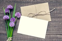 Blank white greeting card with purple wildflowers bouquet and envelope over rustic wooden background