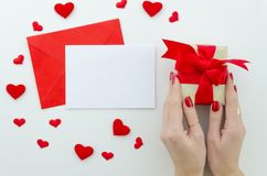 Blank white greeting card with red envelope and gift box in female`s hands. royalty free stock images