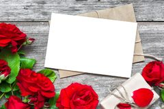 Blank white greeting card with red rose flowers bouquet and envelope with gift box Stock Photo