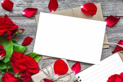 Blank white greeting card with red rose flowers bouquet and envelope with petals, lined notebook and gift box Stock Images