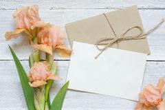 Blank white greeting card with tender iris flowers bouquet and envelope. With flower buds on white wooden background. top view. mock up Royalty Free Stock Image