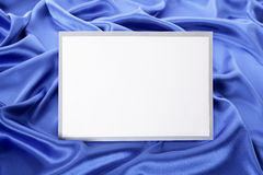 Blank white greetings card or invitation with blue satin background, copy space Stock Image