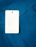 Blank white hang tag on blue fabric Royalty Free Stock Photo