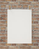 Blank white hanging poster with clothespin and rope on brick wall, background Royalty Free Stock Photo