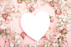 Blank white heart-card with gypsophila flowers and roses on pink