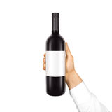 Blank white label mock up on black bottle of red wine in hand is Stock Image