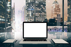 Blank white laptop screen on glassy table in modern office with Royalty Free Stock Photo