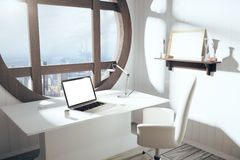 Blank white laptop screen on white table with chair and round wi Royalty Free Stock Photo