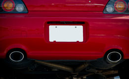 White license plate on red car. Blank white license plate on rear of red car Stock Photography