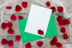 Blank white love letter and envelope with red rose petals on shabby white netting background Royalty Free Stock Images