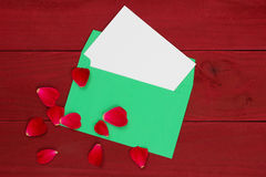Blank white love letter in green envelope with red rose petals on wooden background Stock Images