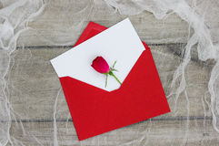 Blank white love letter and red envelope with single red rose Royalty Free Stock Photo