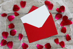 Blank white love letter and red envelope surrounded by red rose petals Royalty Free Stock Photos