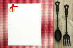 Blank white menu sign on red checkered tablecloth with cast iron spoon and fork Royalty Free Stock Photo