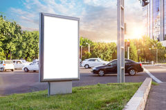 Blank white mock up of vertical light box in a bus stop in beautiful weather and sunshine Royalty Free Stock Images