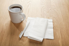 Blank White Napkin or Serviette and Pen and Coffee. White napkin or serviette and pen on oak surface, ideal for notes and phone numbers, and that great idea you Stock Images