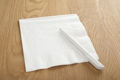 Blank White Napkin or Serviette and Pen on Wooden Surface. White napkin or serviette and pen on oak surface, ideal for notes and phone numbers, and that great Royalty Free Stock Images