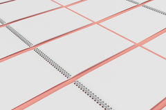 Blank white notebook with metal spiral bound on red background. Grid of open sketchbooks. Business or education mockup. 3D rendering illustration Stock Images