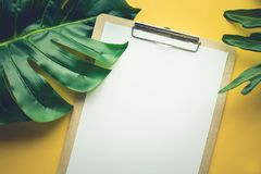 Blank white notepaper with tropical leaves laying on yellow Stock Images