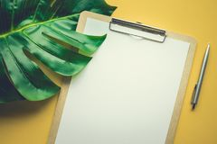 Blank white notepaper with tropical leaves laying on yellow table Royalty Free Stock Image