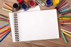Blank white open book on school desk with pencils, art, craft equipment.  Copy space. Blank white folded art book on a school desk with various paints, crayons Stock Photo