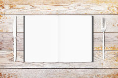 Blank white opened diary with knife and fork on wooden table, mo Royalty Free Stock Photo