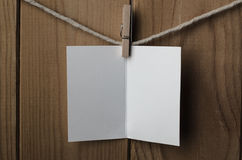 Blank White Opened Greetings Card Pegged to String. An opened, blank, plain white greetings or Christmas card, pegged to string against wood plank background stock photo