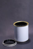 Blank White Paint Tin With Lid. A White Paint tin containing black paint on a dark grey background Stock Photos