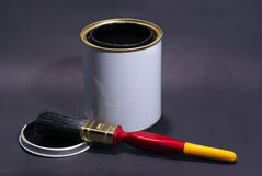 Blank White Paint Tin With Paintbrush and Lid in the Foreground Stock Photo