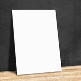 Blank white paper on the black wall and the wooden floor,Mock up Stock Photo