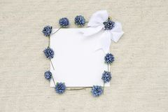 Blank white paper card and blue paper flower with white ribbon on canvas fabric texture background royalty free stock photo