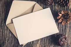 Blank white paper card with brown envelop. And pine cones on old wooden table with vintage and vignette tone Royalty Free Stock Images
