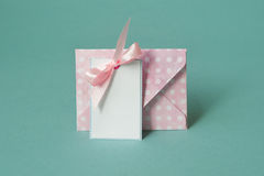 Blank white paper card with With a pink bow under envelop On a turquoise background. Blank thank you or greeting card and envelope Royalty Free Stock Image