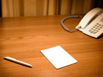 Blank white paper on the desk. Blank white paper on the wooden working desk with the pen and telephone stock photo