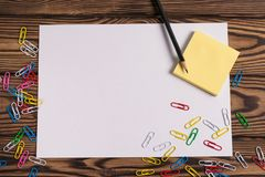 Blank paper and empty yellow square stickers and lot of colored paper clips and one black pencil on old wooden brown worn ta. Blank white paper and empty yellow stock photos