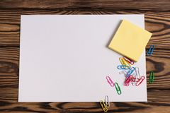 Blank paper and empty yellow square stickers and lot of colored paper clips on old wooden brown worn table. Blank white paper and empty yellow square stickers royalty free stock photo