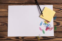 Blank paper and empty yellow square stickers and lot of colored paper clips and one black pencil on old wooden brown worn ta. Blank white paper and empty yellow stock images