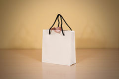 Blank white paper gift bag with a bow mock up standing on a wood Royalty Free Stock Images