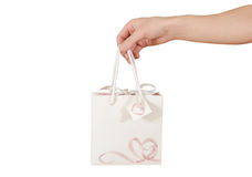 Blank white paper gift bag with hearts mock up holding in hand. Stock Image