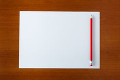 Blank white paper. And pencil on a wooden desk royalty free stock photo