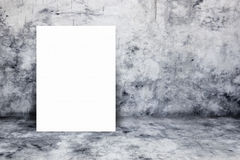 Blank white paper poster lean at bare concrete wall. For text input or according to your design Stock Photo
