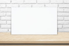 Blank white paper poster over wood table and  brick wall background Stock Images