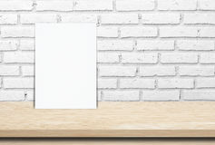 Blank white paper poster over wood table and  brick wall background Royalty Free Stock Image