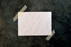 Blank white paper on rough black surface. A crumpled blank piece of paper taped by its corners to a rough black surface, for use as a background royalty free stock images