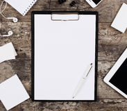 Blank white paper sheet in a clip folder surrounded by office supplies Royalty Free Stock Photography