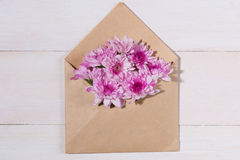 Blank white paper tag with brown envelope and pink flowers on wo Royalty Free Stock Photos