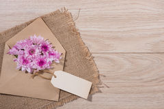 Blank white paper tag with brown envelope and pink flowers on wo. Oden table Royalty Free Stock Images