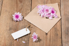Blank white paper tag with brown envelope and pink flowers on wo. Oden table Stock Photos