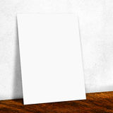 Blank white paper on the white wall and the wooden floor,Mock up Stock Image