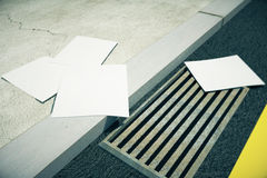 Blank white papers on city pavement Stock Photo